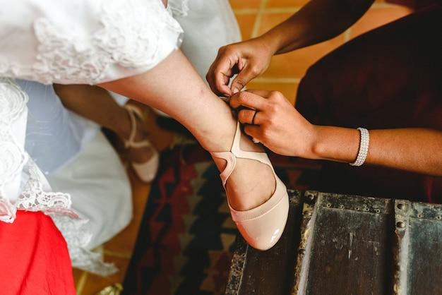 A dama de honra ajuda a noiva a colocar os sapatos. Foto Premium