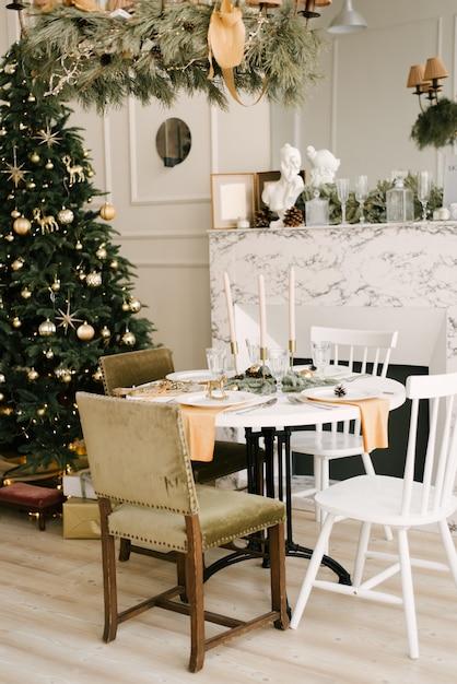 A decoração de natal e ano novo. sala de estar com árvore de natal, lareira e mesa festiva Foto Premium
