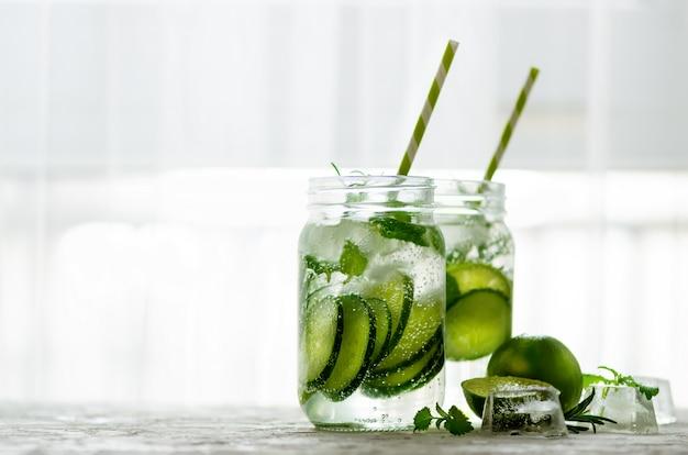 A desintoxicação fria e refrescando molha com cal, pepino, alecrins e gelo no frasco de vidro. copyspace Foto Premium