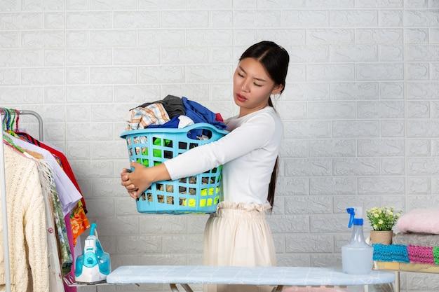 A dona de casa cansada está cansada das roupas da cesta com um tijolo branco. Foto gratuita