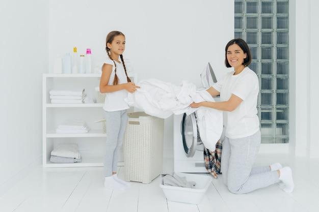A dona de casa contente lava-se com pouco ajudante adorável. mãe e filha lavam as roupas na lavanderia, carregam a roupa na lavadora. mulher fica de joelhos perto da máquina de lavar. conceito de trabalho doméstico Foto Premium