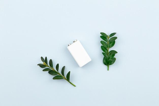 A energia de eco ou a ilustração das energias verdes com uma bateria e os ramos brancos saem em um fundo claro com o espaço da cópia para o texto. Foto Premium