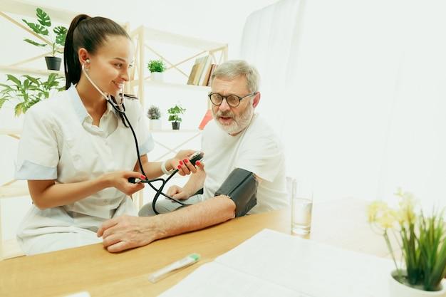 A enfermeira visitante ou o visitante de saúde cuidando de um homem idoso Foto gratuita