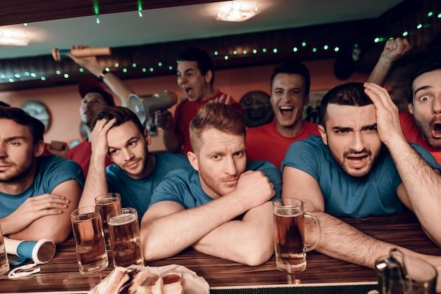A equipe azul triste ventila na barra na barra com equipe vermelha. Foto Premium
