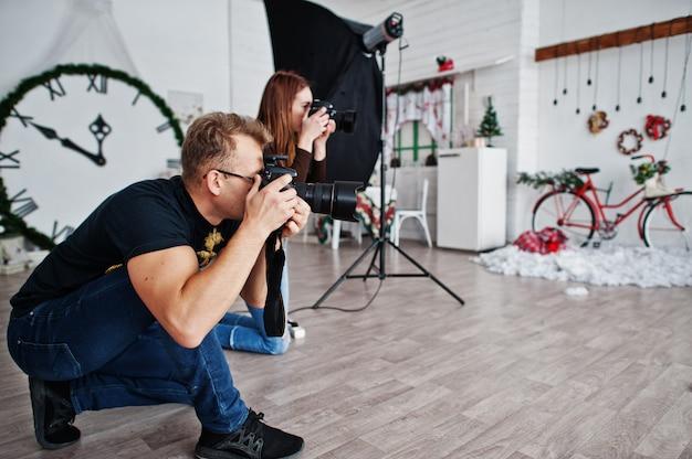 A equipe de dois fotógrafos atirando no estúdio. fotógrafo profissional no trabalho. Foto Premium