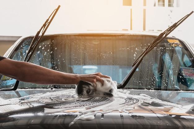 A equipe de lavagem de carros está usando uma esponja umedecida em água e sabão para limpar o carro. Foto Premium