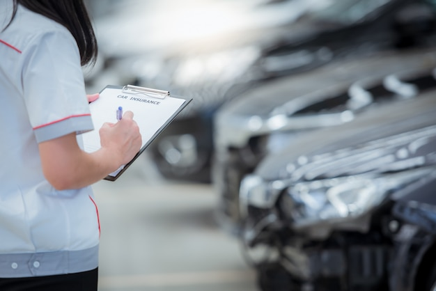 A equipe do agente de seguros escreve na área de transferência enquanto verifica o carro depois de ser avaliada e procede à reivindicação do acidente - o carro possui seguro contra acidentes. Foto Premium