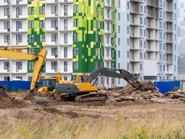 A escavadeira cava o terreno para a fundação e construção de novos edifícios. Foto Premium