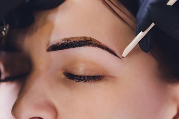 A esteticista- maquiadora aplica hena de tinta nas sobrancelhas aparadas, desenhadas e previamente arrancadas em um salão de beleza na correção da sessão. cuidado profissional para o rosto. Foto Premium