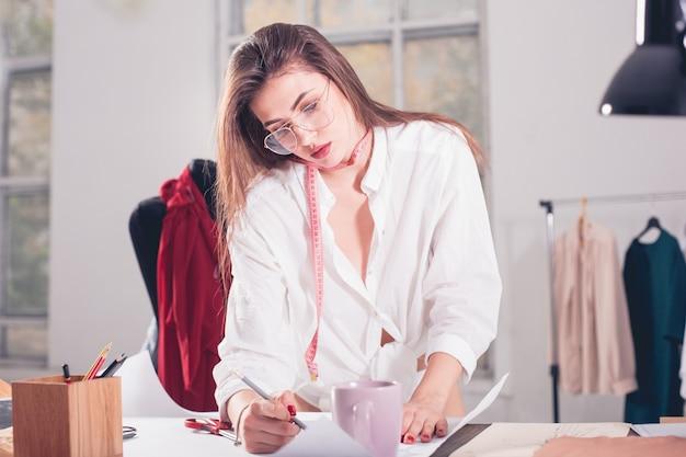 A estilista feminina trabalhando sentada na mesa Foto gratuita