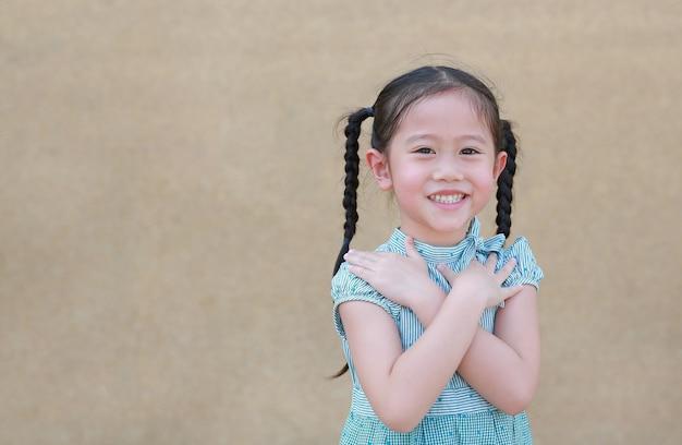 A expressão asiática pequena feliz da menina da criança cruza seus braço e sorriso. crianças confiantes e alegres. Foto Premium