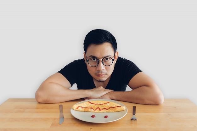 A face séria do homem asiático está comendo o grupo caseiro do café da manhã da omeleta. Foto Premium