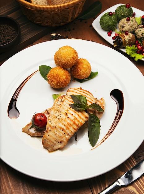 A faixa salmon cozida com batatas e queijo rola, e mistura dos vegetais. Foto gratuita