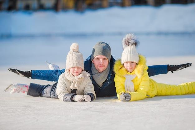 A família aprecia o inverno na pista de gelo ao ar livre Foto Premium