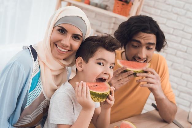 A família árabe está comendo uma melancia em sua cozinha. Foto Premium