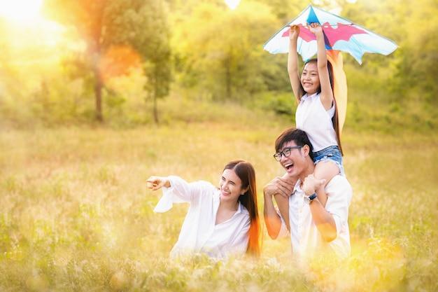 A família asiática pai, mãe e filha jogam ta pipa no parque ao ar livre Foto Premium
