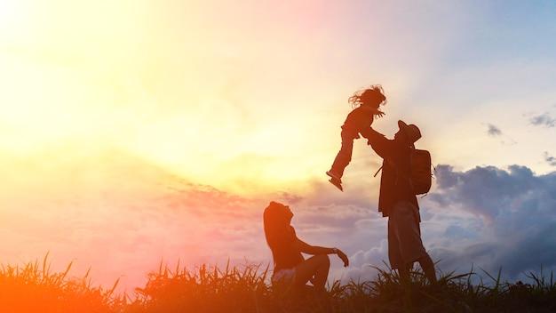 A família feliz de três pessoas, mãe, pai e filho na frente de um céu do por do sol. Foto Premium