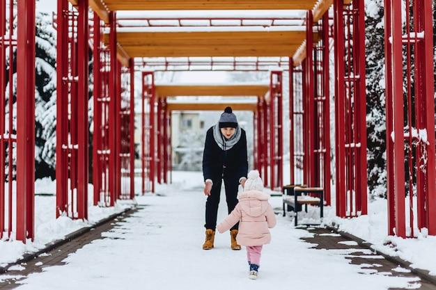 A família nova feliz anda com o bebê na rua do inverno, mamã, paizinho, criança Foto Premium
