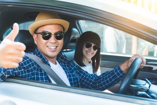 A felicidade asiática nova dos pares da vista lateral que senta-se na feira automóvel manuseia acima. Foto Premium