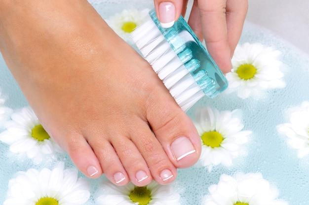 A fêmea lava e limpa as unhas dos pés com água usando uma escova de limpeza Foto gratuita