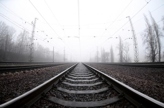 A ferrovia em uma manhã nublada. um monte de trilhos e dormentes ir para o horizonte enevoado Foto Premium