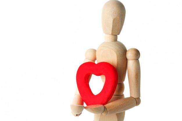 A figura de madeira de um homem tem nas mãos um coração vermelho sobre uma superfície branca, dá o coração Foto Premium