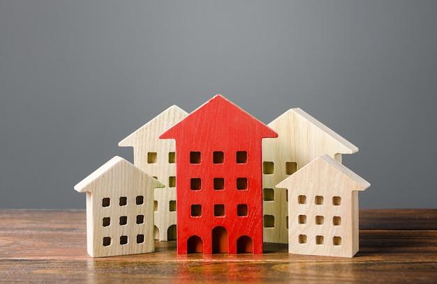 A figura vermelha de um edifício residencial se destaca entre as demais casas. Foto Premium
