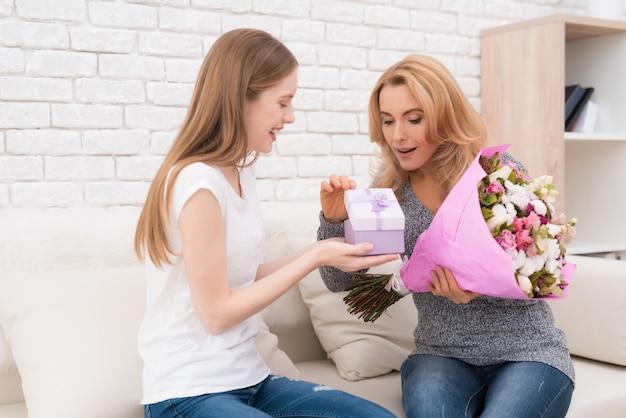 A filha dá à mãe flores e presentes. Foto Premium
