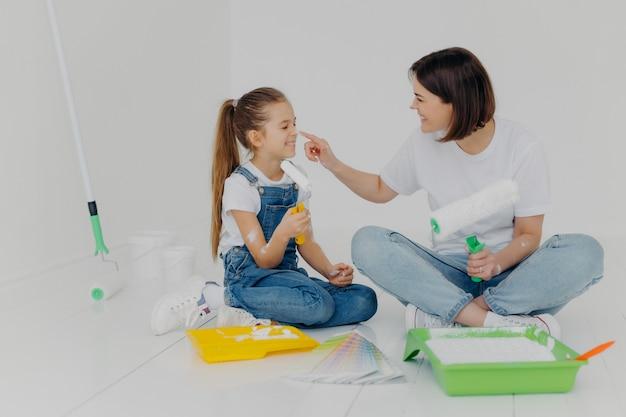A filha e a mãe amigáveis positivas esfregam-se com tinta branca Foto Premium