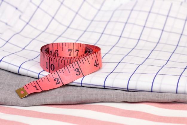 A fita métrica está em tecido de algodão. conceito de costura, costura de tecidos naturais. Foto Premium