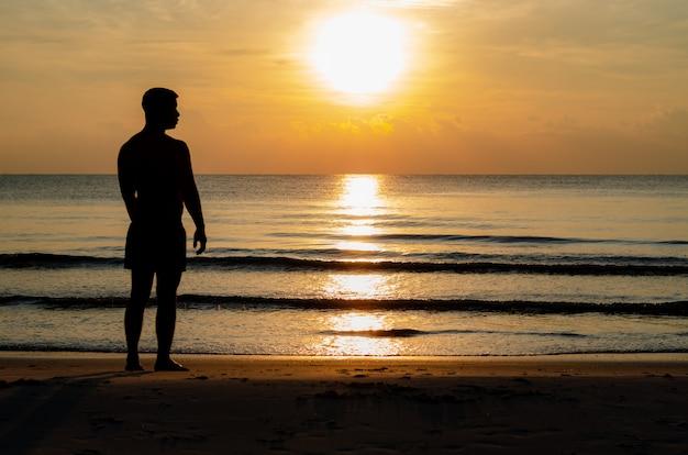 A foto da silhueta de um homem que está sozinho na praia aprecia o momento do nascer do sol. Foto Premium