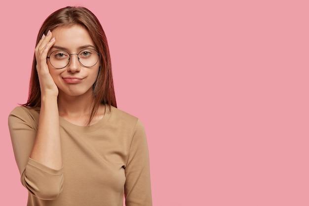 A foto horizontal de uma mulher adorável aborreceu a expressão facial descontente, parece descontente, usa óculos redondos e suéter casual, isolada sobre uma parede rosa com um espaço de cópia em branco de lado Foto gratuita
