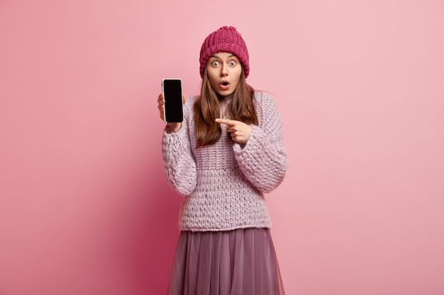 A foto interna de uma garota milenar surpresa mostra a tela do seu smartphone e exibe um ótimo aplicativo de edição de fotos Foto gratuita