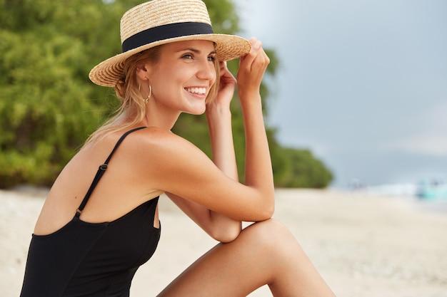 A foto lateral de uma jovem turista feliz e adorável usa maiô preto e chapéu de verão, toma banho de sol na praia, admira a vista maravilhosa do oceano e tem uma expressão positiva. conceito de pessoas e recreação Foto gratuita