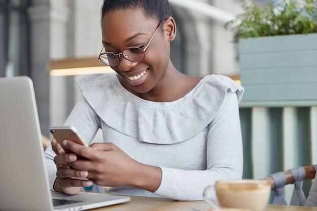 A foto recortada de um redator feminino satisfeito lê informações positivas no telefone inteligente, senta-se em frente a um laptop aberto e bebe café aromático. Foto gratuita