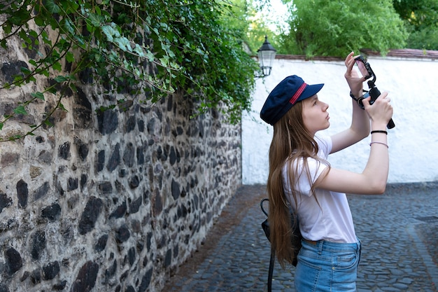 A fotógrafa procura um bom ângulo para tirar fotos na rua. Foto Premium