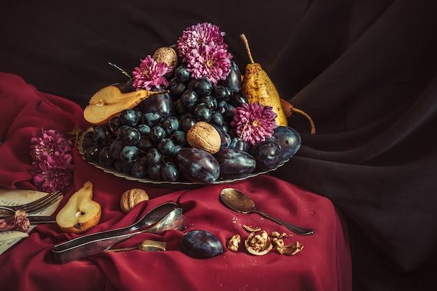 A fruteira com uvas e ameixas contra uma toalha de mesa marrom Foto gratuita