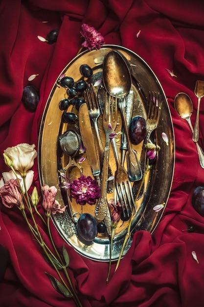 A fruteira com uvas e ameixas em chapa de prata Foto gratuita