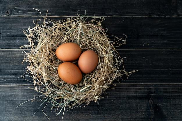 A galinha marrom fresca eggs no ninho do feno no fundo de madeira preto. Foto Premium