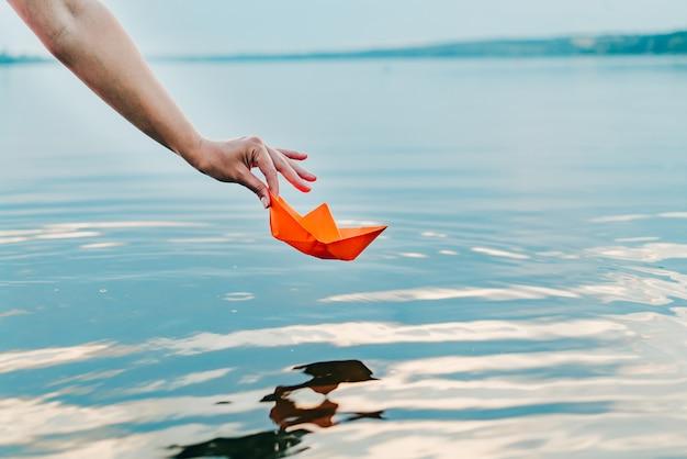 A garota abaixa seu barquinho de papel na água com a mão. um navio laranja está pendurado sobre o rio Foto Premium