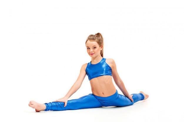 A garota adolescente fazendo ginástica exercícios isolados na parede branca Foto gratuita