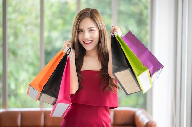 A garota bonita de vestido vermelho gosta de fazer compras. ela tem muitas sacolas e as compra de su Foto Premium