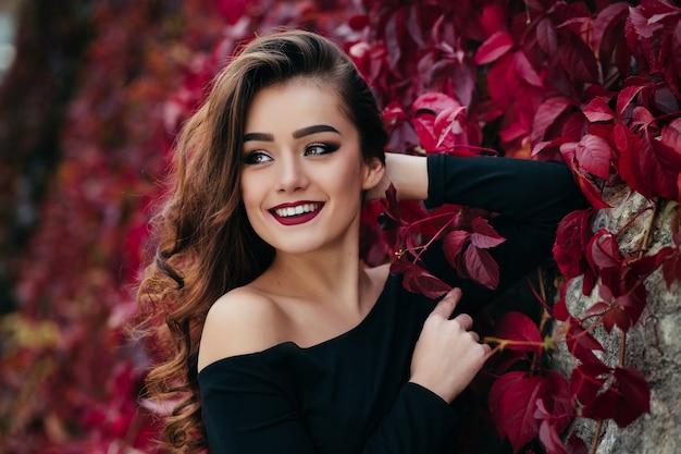 A garota bonita fica perto walll com folhas Foto gratuita