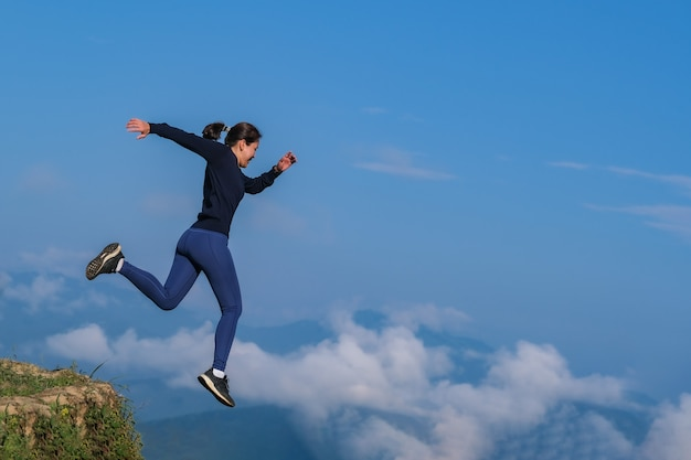 A garota correu, pulou de um lugar alto e correu em um campo montanhoso. Foto Premium
