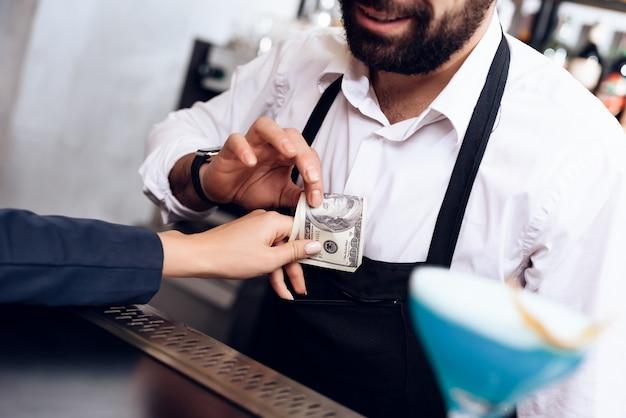 A garota dá o pagamento de barman para o pedido. Foto Premium