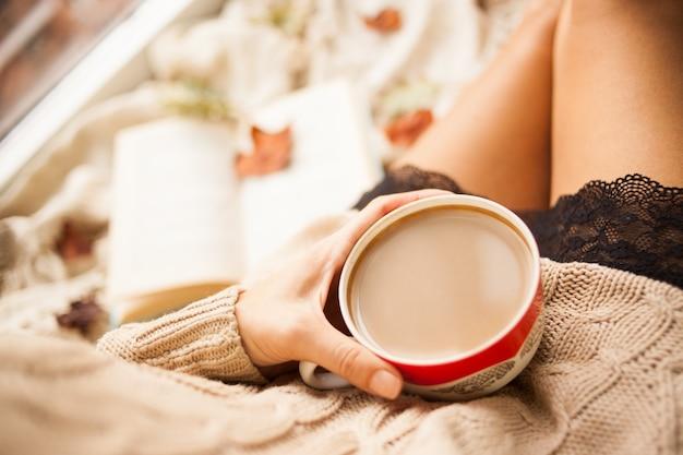 A garota em uma camisola de malha aconchegante beber café de uma caneca vermelha Foto Premium