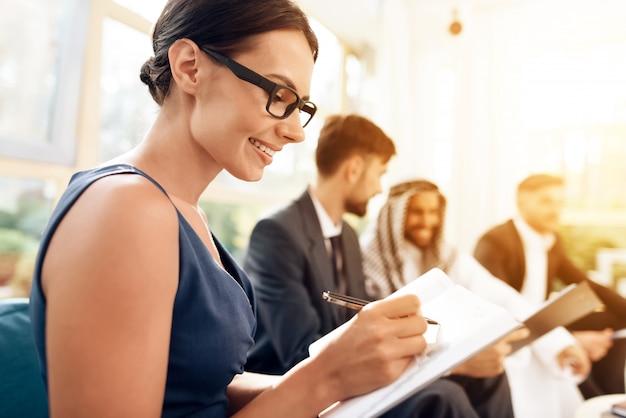 A garota escreve uma caneta no papel durante uma reunião com o árabe. Foto Premium
