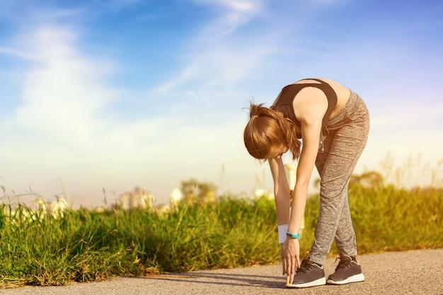 A garota está esticando o corpo antes de correr de manhã. Foto Premium