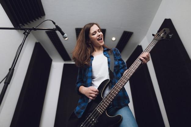 A garota está gravando uma música em um estúdio de gravação moderno. Foto Premium