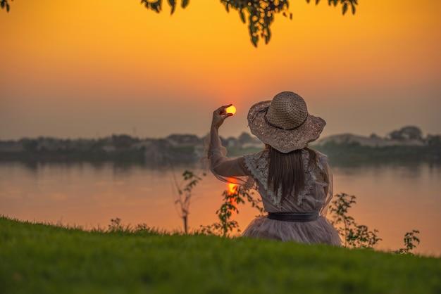 A garota está sentada apreciando o pôr do sol. as mulheres pegam o sol Foto Premium